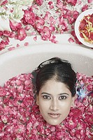 High angle view of a young woman lying in a bathtub covered with flower petals