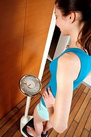 Woman weighing herself on scales in the locker room