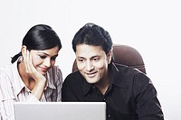 Close-up of a businessman and a businesswoman working on a laptop