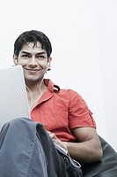 Low angle view of a young man wearing headphones using a laptop