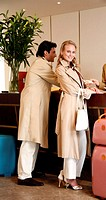 Couple checking in at hotel reception (thumbnail)