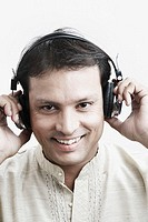 Portrait of a mid adult man wearing headphones listening to music