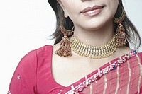 Close-up of a mid adult woman wearing a necklace and earrings