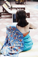 Rear view of a young woman using a laptop