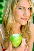 Woman eating green apple (thumbnail)