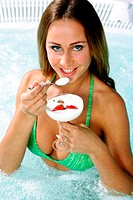 Woman enjoying a glass of milk and strawberries in the pool