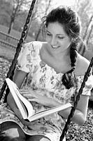 Woman reading book while sitting on the swing
