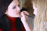 Woman applying colour on her friend's lips