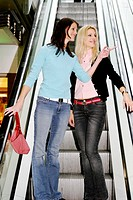 Two women standing on the escalator