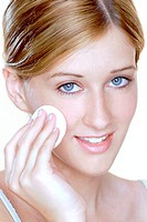 Woman applying powder foundation on her face