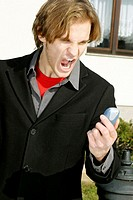 Businessman screaming into his mobile phone
