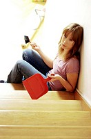 Woman sitting on the stairs holding a brush and a dustpan