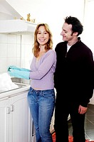 Man watching his wife washing dishes
