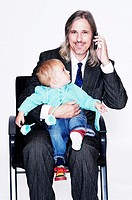 Businessman taking care of his son while talking on the mobile phone