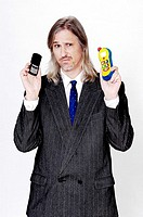 Businessman holding a real and a toy mobile phone