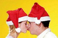 Couple in christmas hats kissing