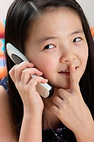 Girl showing a hushing sign while talking on the handphone.
