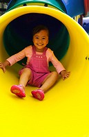 Girl smiling while sliding down from a slide.