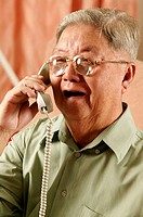 Bespectacled old man talking on the phone
