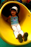 Girl sliding down from a slide.