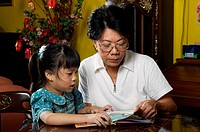 Woman reading story for her granddaughter.