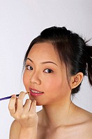 Woman applying colour on her lips with a brush.