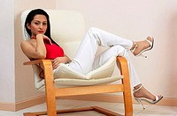 Woman posing whie sitting on a chair.