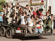 A trailer filled with press photographers travels in front of a car carrying a celebrity in a parade in Austin. Texas. USA.