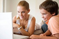Brother and sister using laptop