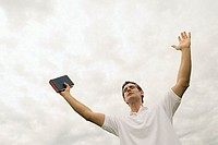 Man holding the bible with arms raised
