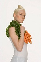 Young woman holding carrots