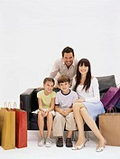 Family on sofa with shopping bags