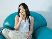 Young good looking asian girl posing with a green apple