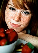 Freckled woman in front of a bowl of strawberries