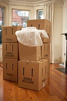 Packing boxes marked fragile, stacked in living room
