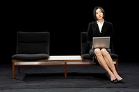 Businesswoman sitting on bench using laptop, tilting head to one side
