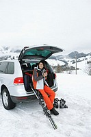 Man sitting on boot of car by skis on snow, holding thermos