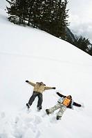 Two men lying in snow field