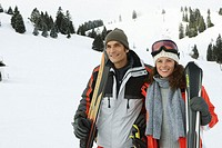 Couple carrying skis on shoulders outdoors, smiling