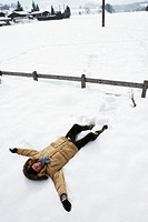 Man lying on snow, arms outstretched, smiling