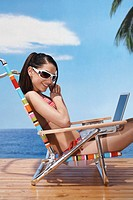 Young woman wearing sunglasses with laptop on beach chair
