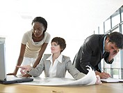 Businesswomen looking at plans on desk and laptop, man on phone