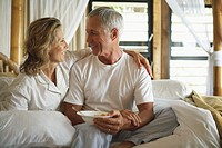 Senior woman with arm around man with bowl in bed, close-up