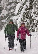 Man and woman snowshoeing through powder snow