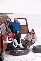 Four young adults with inner tubes drinking hot beverages beside van
