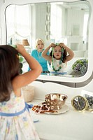 Girl (2-4) trying on necklace in mirror, grandmother in background