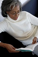 Senior woman reading book, elevated view, close-up