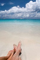 US Virgin Islands, St. John, couple lying on beach, low section