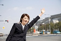 Young businesswoman holding out hand on street