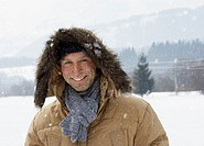 Man wearing hooded jacket in snows covered landcape, smiling, portrait